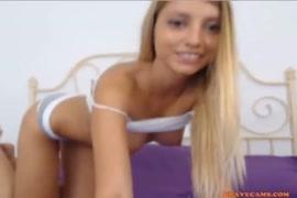 Une adolescente blonde joue avec un jouet sexuel.